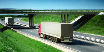 Two lorries driving under a bridge